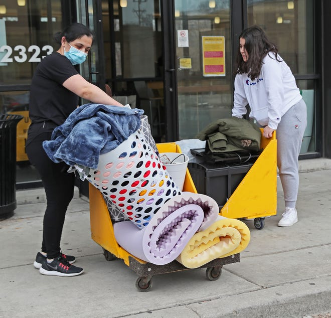 March 27 2020, Rano Atambaeua of Kenosha, left, helps move her daughter Sevinch Atambaeua out of the UW-Milwaukee Cambridge Commons dormitory. UWM is staggering the move dates for each dormitory.