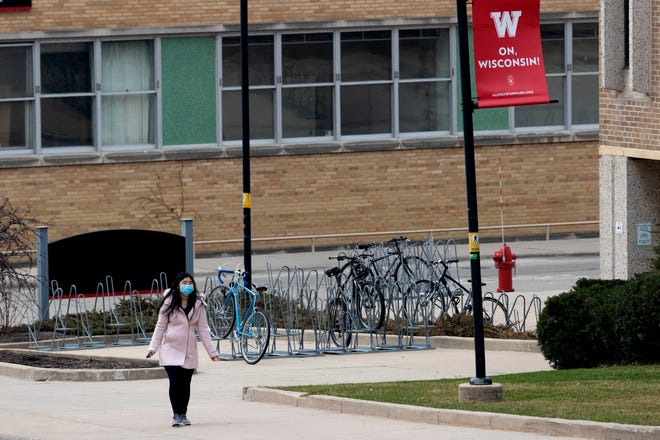 A student wears a face mask on UW-Madison's campus. The UW System estimates the pandemic has cost it nearly $170 million as of April 10.