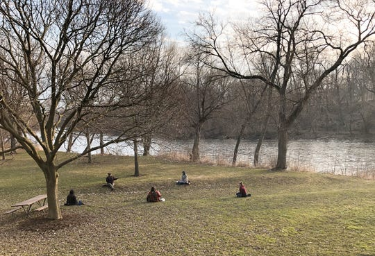 A group of friends practice social distancing while visiting Hubbard Park along the Milwaukee River in Shorewood on Wednesday, March 25, 2020.