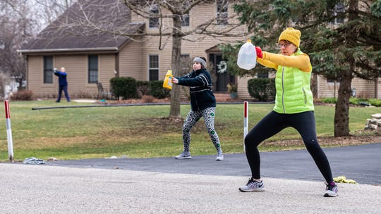 Menomonee Falls resident Maureen Lewis, right, leads an outdoor morning exercise routine with her daughter Carolyn and a neighbor, left, following along on Friday, March 27, 2020. Maureen stands in the street so participants can see her from their driveways while observing social distancing. The workout includes light stretches and exercises for 10 to 15 minutes.