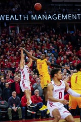 Wisconsin's Brad Davison lofts his game-winning three over Maryland's Darryl Morsell in the waning moments of the teams' game on Jan. 14.