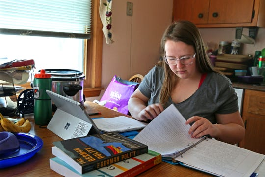 Jennifer Morzfeld, a junior and political science major at UW-Madison, works on a class assignment on March 25 at her Milwaukee home. Morzfeld normally works three jobs to pay for rent and other expenses at her apartment and is among the many who are unable to work because of the coronavirus pandemic.