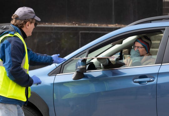 Poll worker Jon Becker, left, assists a woman taking advantage of drive-up voting Friday, March 27, 2020 in Madison, Wis. Voters who are high-risk for COVID-19 can register to vote and/or cast their ballot from their vehicle. High-risk populations include older adults and people with chronic health conditions.