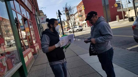 Wind of the Spirit volunteers talk to residents in downtown Dover about the coronavirus outbreak and community resources.