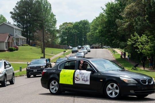 Daniel Pratt Elementary School teachers and their families caravan through the schools neighborhood to wave to students in Prattville, Ala., on Friday, March 27, 2020.