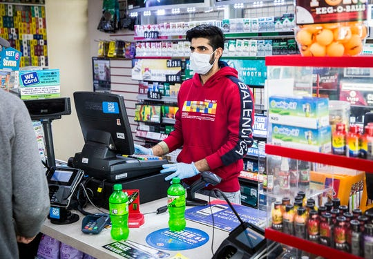 A gas station attendant works in gloves and a mask on University Avenue.
