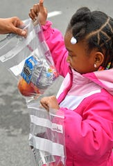 Toriana Word, 6, checks out the breakfast and lunch she received from a school bus making deliveries in her neighborhood March 25, 2020.