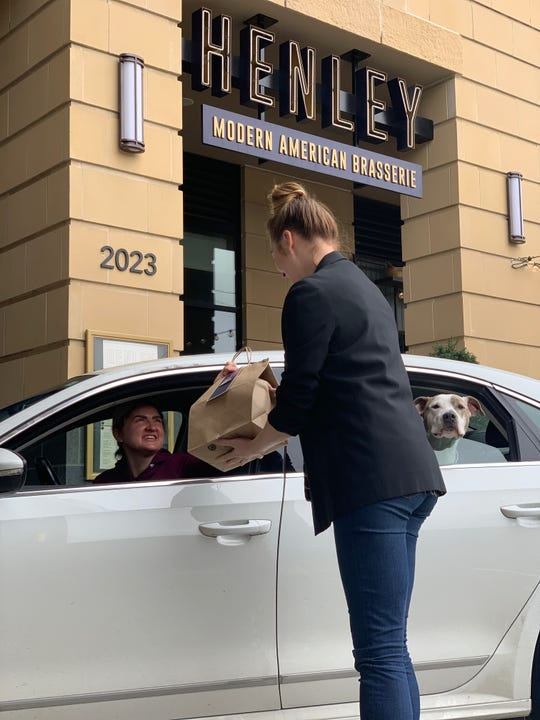 Jenelle Engleson, assistant general manager/sommelier at midtown Nashville restaurant Henley, delivers curbside take-out food to customer Jenny Walsh March 26, 2020. Henley is one of hundreds of Middle Tennessee restaurants adding curbside to-go service during the coronavirus pandemic.