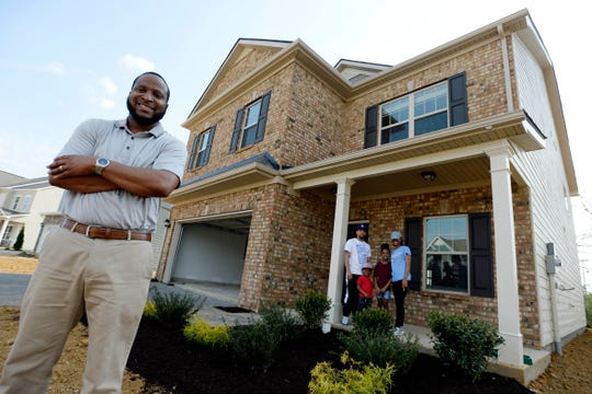 Bobby Smith of Park Realty, left, stands with Sadaricus Bowers; his wife Sasha, right, and children, Saniyah and Aycens, in front of their new home on Friday, March 27, 2020, in Murfreesboro, Tenn. Smith says his work in the residential real estate business is modified because of the corona virus. Open houses are canceled but individual home showings are continuing.