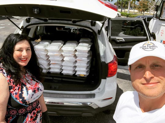 David Yarinsky , owner of the Great Foodini's Mobile Bistro, and Jessica Lee Dang stand in front of 66 meals ready to be delivered to Habitat or Humanity. The Great Foodini's Mobile Bistro food truck is delivering 350 meals a day to hungry children in Collier County during the COVID-19 outbreak.