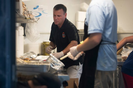 Todd Brooks, owner of Brooks Gourmet Burgers & Dogs, puts  orders together for NCH Baker health care workers, Thursday, March 26, 2020,  in front of the Naples Community Hospital's Telford Library in Naples.