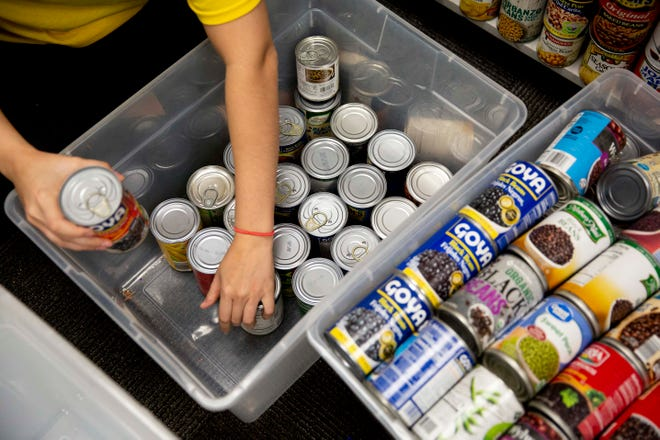 Alexis Rodriguez, community impact coordinator with United Way, packs canned goods into boxes at South Fort Myers High School on Friday, March 27, 2020.