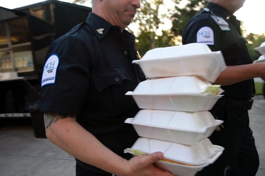 NCH Baker security team carry away dinner for themselves and their staff, Thursday, March 26, 2020, in front of the Naples Community Hospital's Telford Library in Naples. Brooks Gourmet Burgers & Dogs provided a free meal to hospital staff members as a way to say thank you to health care workers and staff at NCH Baker.