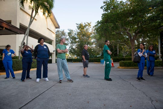 NCH Baker staff line up to receive a free meal, hosted by Brooks Gourmet Burgers & Dogs, Thursday, March 26, 2020, in front of the Naples Community Hospital's Telford Library in Naples.