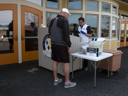 Hung Chow, general manager of Virtues Golf Club, checks golfers in at a temporary outdoor check-in on Thursday afternoon. Following the Licking County Health Department's ruling Friday, courses can remain open, but carts cannot be used, and all registration must be done online.