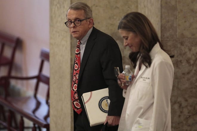 Ohio Gov. Mike DeWine, left, and Dr. Amy Acton, director of the Ohio Department of Health, leave the State Room before their daily update on the states response to the ongoing COVID-19 pandemic on Thursday, March 26, 2020 at the Ohio Statehouse in Columbus, Ohio.