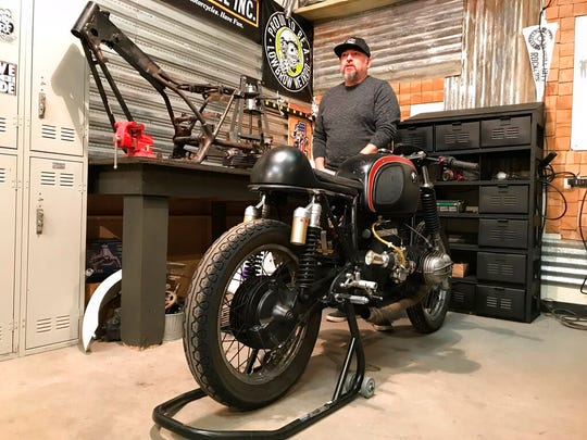 In this Jan. 24, 2020, photo, Steven Maes stands at his Rust Is Gold Garage and Coffee shop in Albuquerque, next to his vintage BMW motorcycle. Maes recently was laid off from a movie production in Albuquerque and was forced to layoff four of his employees thanks to the downturn caused by the novel coronavirus.