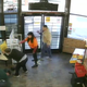 In this till from surveillance camera, Lorraine Provencio, holding the caution sign, watches as Canaan Bower and Daniel Beltran Arroyo stuggle on the floor of Chucky's Gas Station in Doña Ana on Wednesday, March 25, 2020. Two customers also stand watch.