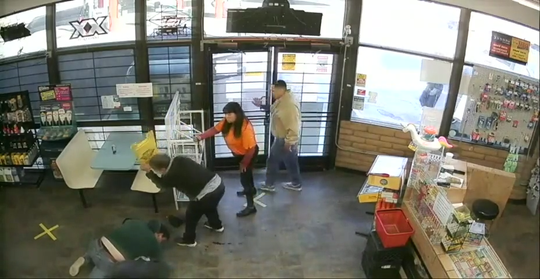 In this still from surveillance camera, Lorraine Provencio, holding the caution sign, watches as Canaan Bower and Daniel Beltran Arroyo stuggle on the floor of Chucky's Gas Station in Doña Ana on Wednesday, March 25, 2020. Two customers also stand watch.