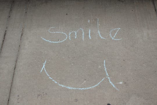A chalk art sign encourages Artesia residents to smile during the COVID-19 coronavirus.