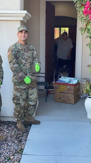 Ben Martino, 92, salutes California National Guard soldiers who delivered food to him and his wife earlier this week in Indio.