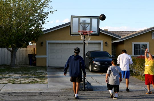 Jojo Labuen, 9, right, shoots the basketball as he and his brothers take an outdoor break from sheltering-in-place to play basketball in front of their house in Palm Springs, Calif., on Thursday, March 26, 2020.