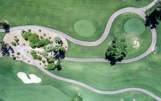 A winding golf cart path sits unusued during one of golf's busiest times of the year in the Coachella Valley as the coronavirus disrupts regular life at the Indian Wells Golf Resort, March 25, 2020.