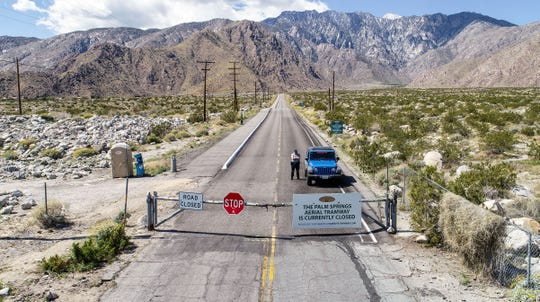 A security officer keeps vehicles from traveling up to the Palm Springs Aerial Tramway after it was shut down because of the coronavirus, March 27, 2020.