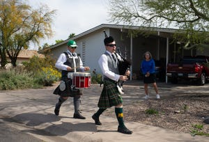 Thomas Rowley (center) and Jaymes Rowley march down the sidewalk on March 26, 2020, as they perform in a Tempe neighborhood. Looking on from her driveway is Joni Ward.