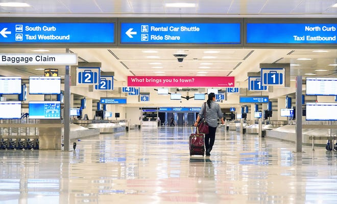 A lone traveler enters an empty baggage claim area in Terminal 4 at Sky Harbor International Airport in Phoenix. Airlines are reducing flights due to the coronavirus COVID-19 outbreak.