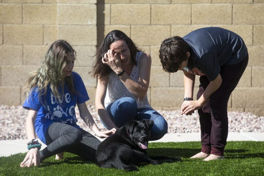 Natalie Kaska (center) and her two children Dillon Kaska, 11, (right) and Makayla Kaska, 13, (left), get acquainted with Augustus in Glendale, Ariz. on March 26, 2020. The Kaskas were sheltering Agustus and a cat named Lucifer for Lost Our Homes Pet Rescue during the COVID-19 pandemic in Arizona.