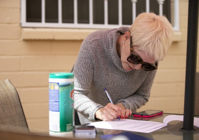 Mary Gates, 70, signs her last will and testament at her Phoenix townhome, on March 26, 2020. Gates does not have coronavirus but has underlying health conditions and says she is certain she will die if she contracts the virus.