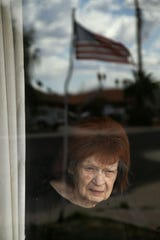 Rose Yozzo, 91, is living alone through the coronavirus pandemic. She has lived alone since her husband passed away two years ago.  She is seen through a window of her Tempe home on March 27, 2020.