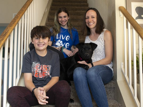 Augustus the puppy sits with his foster family, Natalie Kaska (right) and her two children Dillon Kaska, 11, (left) and Makayla Kaska, 13, (center) in Glendale, Ariz. on March 26, 2020. The Kaskas were sheltering Agustus and a cat named Lucifer for Lost Our Homes Pet Rescue during the COVID-19 pandemic in Arizona.