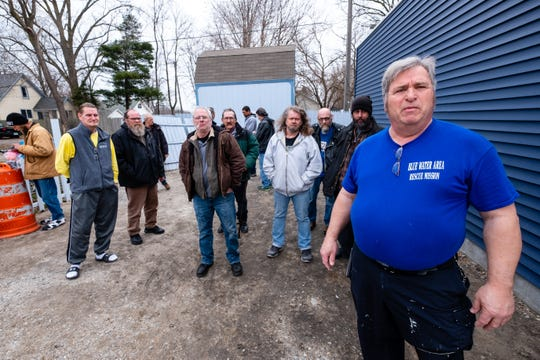 Arnie Koontz, Blue Water Area Rescue Mission executive director, right, stands with a group of men staying at the shelter Thursday, March 26, 2020, in Port Huron. Koontz said even with the coronavirus pandemic, he can't legally force them to stay at the shelter.