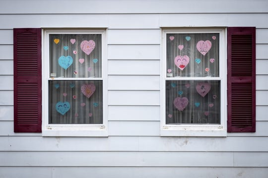 Paper hearts are taped to the window of a Capac home.