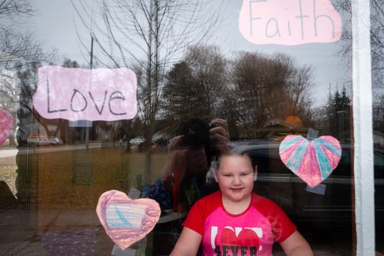 Myla, 6, decorated the window of her family's Capac home with paper hearts and positive words to make people happy during the coronavirus pandemic.