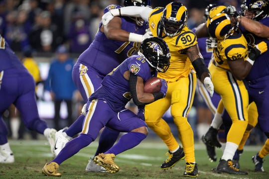 Baltimore Ravens running back Mark Ingram, left, tries to sprint past Los Angeles Rams defensive end Michael Brockers in an NFL football game Monday, Nov. 25, 2019, in Los Angeles. (AP Photo/Kyusung Gong)