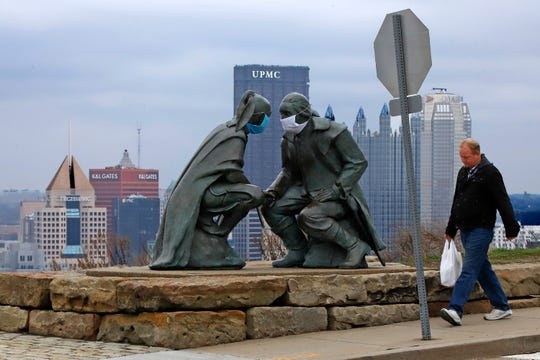"""A man passes by the """"Point of View"""" sculpture depicting George Washington and Seneca leader Guyasuta on Mount Washington, overlooking downtown Pittsburgh, Friday, March 27, 2020."""