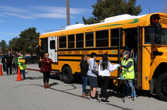 WCSD bus driver Beppy Ziemer, right, helps hand out homework packets for students without access to the internet while at Pine Middle School in Reno on March 27, 2020.