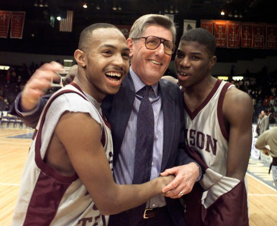 Edison coach Dick O'Toole celebrates with players after the Inventors won the 1998 Section V Boys Basketball Championship, the first in school history.