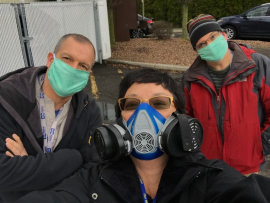 Democrat and Chronicle photographers display the protective gear they are wearing as they cover the coronavirus crisis in Greater Rochester. From left, Jamie Germano, Tina MacIntyre-Yee and Shawn Dowd.
