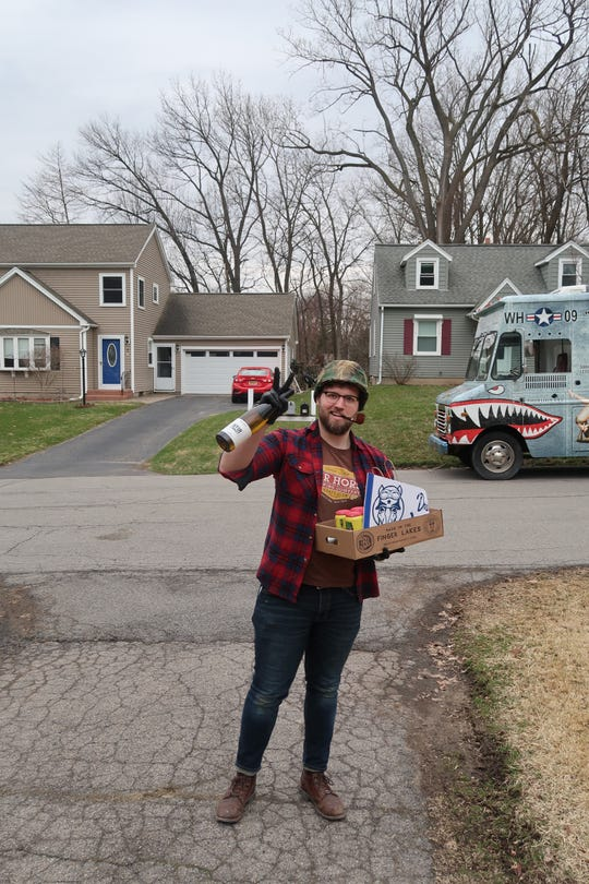 Jon Mansfield of War Horse Brewing stands in beer columnist Will Cleveland's driveway Thursday as he makes a home delivery.
