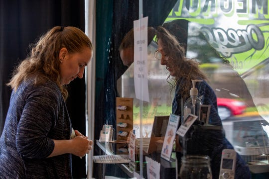 Customer Karen Webb browses a cannabis menu handed to her by manager Missy Roberts, protected by a glass window, at Oregon Homegrown in West Salem on March 27, 2020.