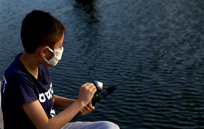 Felipe Vargas wears a mask to protect against coronavirus as he fishes off a bridge over the Concho River in downtown San Angelo on Thursday, March 26, 2020.