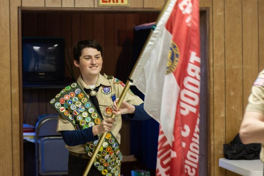 Nathaniel Long carries the Boy Scouts flag during a meeting of  Troop 314 in March.