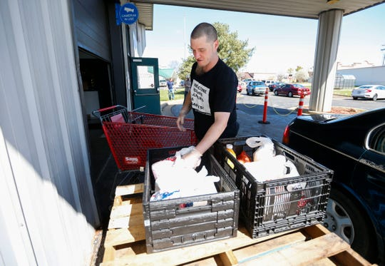 Michael Dickey, a Crosslines volunteer from Freedom City Church, unloads groceries into a bin for drive-thru customers to the food pantry on Wednesday, March 25, 2020. Crosslines has changed to drive-thru service due to the coronavirus.