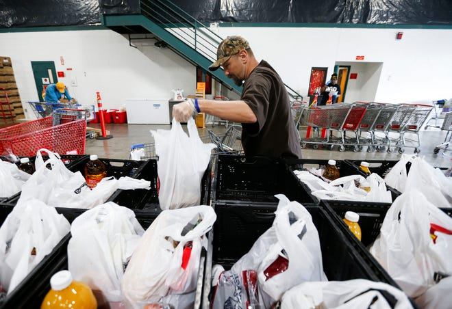 Jason Jones, a Crosslines volunteer from Freedom City Church, unloads groceries into a bin for drive-thru customers to the food pantry on Wednesday. Crosslines has changed to drive-thru service due to the coronavirus.