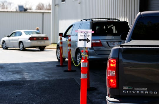 Cars line up at Crossline to pick up food from the food pantry on Wednesday, March 25, 2020. Crosslines has changed to drive-thru service due to the coronavirus.