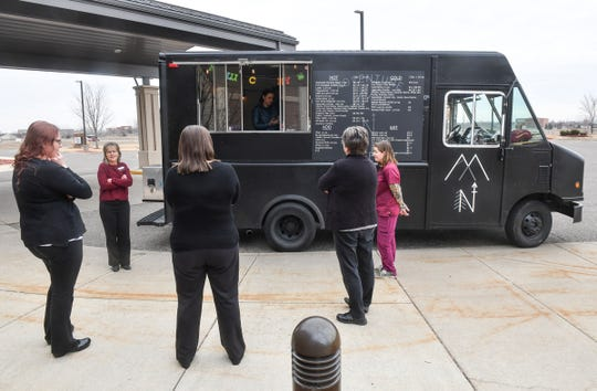 St. Cloud Orthopedics employees smile while waiting for their coffee orders from the Adventure Coffee MN truck Friday, March 27, 2020, in Sartell.